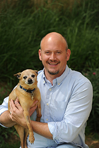 Judah Battista holding a brown Chihuahua