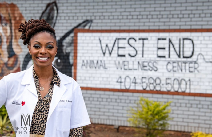 Dr. Ashley Randall, DVM standing in front of a West End Animal Wellness Center sign painted on the brick of a building