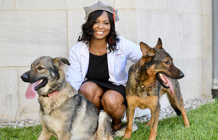 Dr. Tierra Price posing with two shepherd dogs