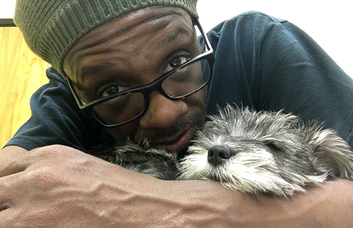 Johnny Jankins snuggling with a small fluffy gray and white dog