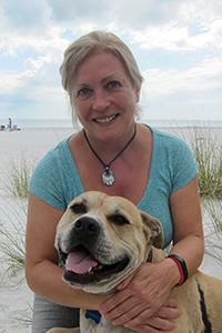 Kathy Stolzenburg with a dog on a beach
