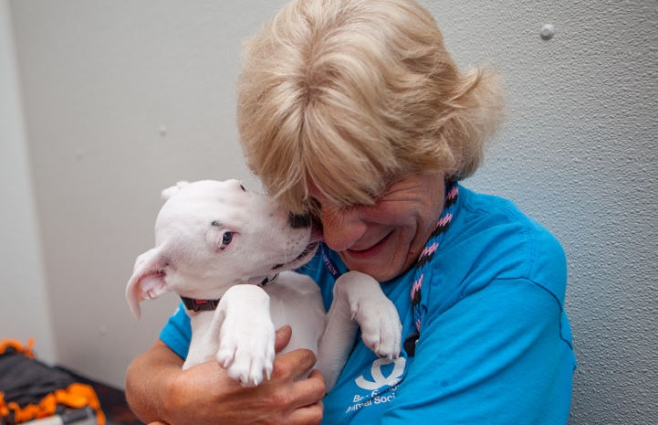 Best Friends volunteer Kathy Posekel snuggling with a white puppy