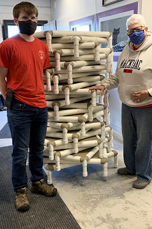 Joseph Wittke and a woman standing next to the stack of dog beds he made and donated to Amazing Grace Animal Rescue