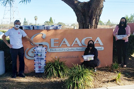 People standing in by the SEAACA sign with stacks of kitten kits