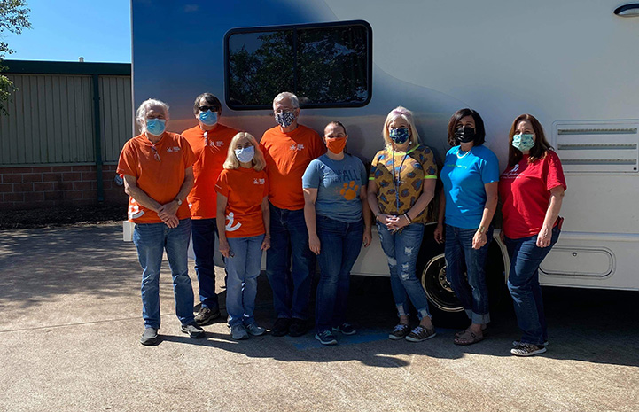 Masked group of people, many wearing Best Friends shirts, posing in front of the transport RV