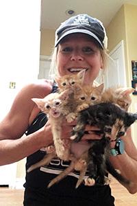 Jill holding an entire litter of foster kittens