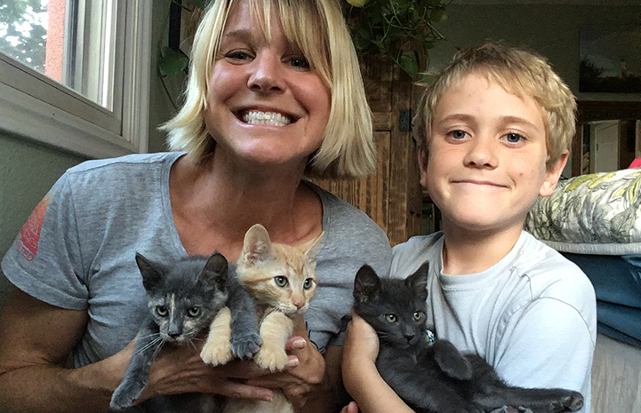 Jill and one of her sons holding three foster kittens