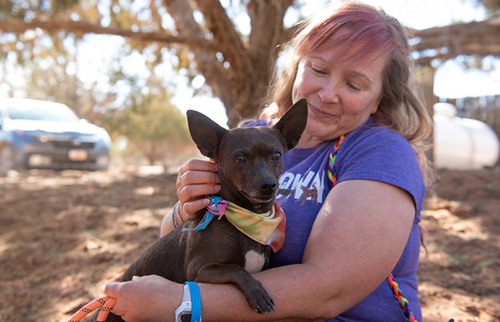 Woman holding BoPeep the dog, who is wearing a bandanna