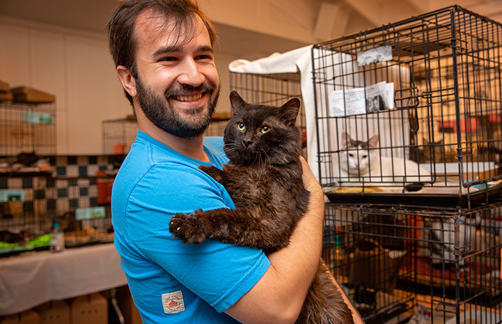 Smiling man holding a dark gray cat at the Best Friends Su-Purrr Adoption event in L.A., with kennels behind them