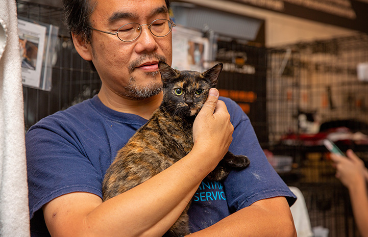 Man snuggling a tortoiseshell cat close to his chest