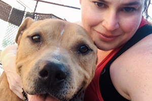 A selfie taken by Tessa of her with Seymour, a brown and white pit bull terrier type dog