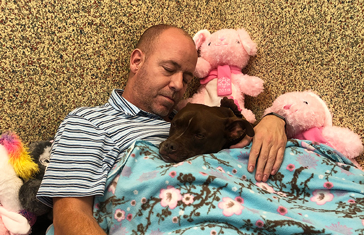 Scott Poore sleeping next to Queen the dog at the shelter