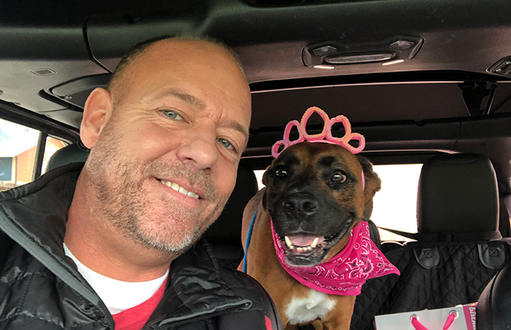 Scott Poore in a car next to a pit bull type dog wearing a tiara