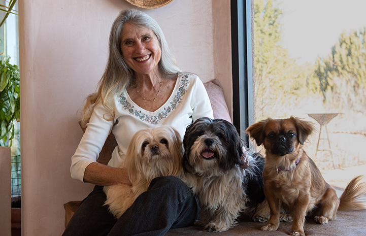 Best Friends co-founder Jana posing with her three small dogs, Sange, Paco and Lula