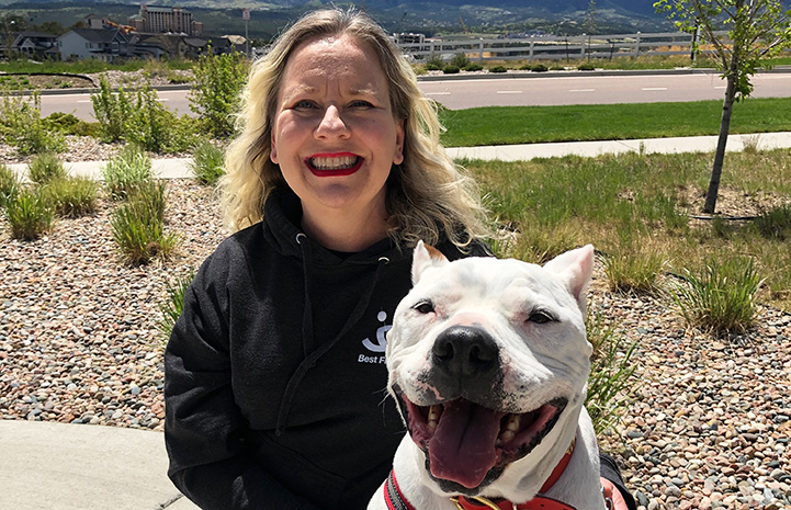 Woman posing with Ralph, the white pit bull terrier with cropped ears
