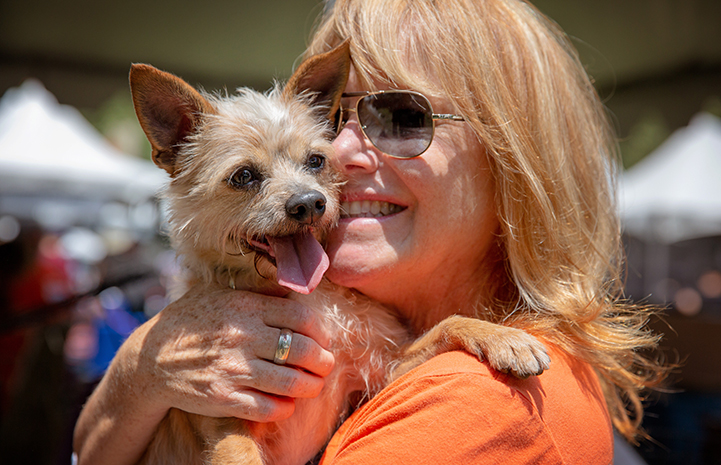 A smiling woman wearing sunglasses and an orange T-shirt, holding a fluffy terrier mix dog whose tongue is out and paw on her shoulder