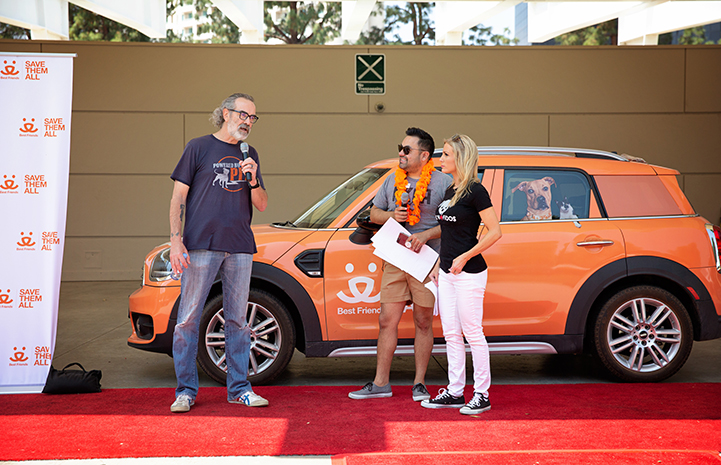 Three people talking in front of an orange Best Friends-branded MINI car at the A tent with human and dog activity at the NKLA Pet Super Adoption