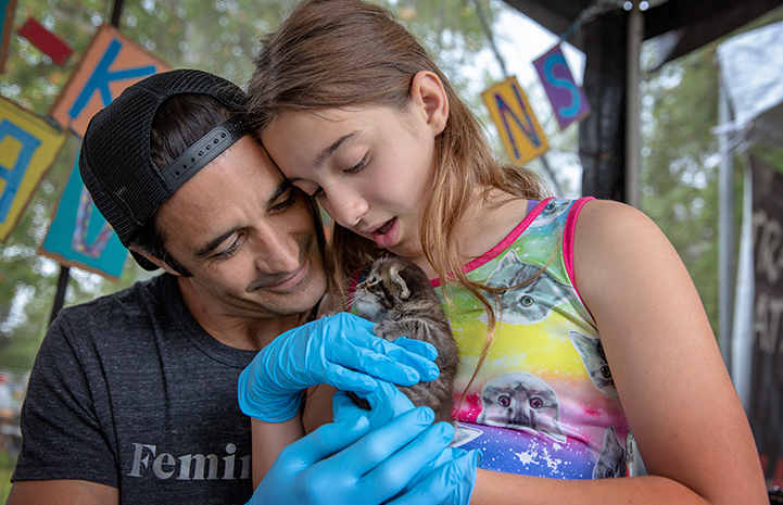 Actor Gilles Marini next to a young girl holding a tabby kitten