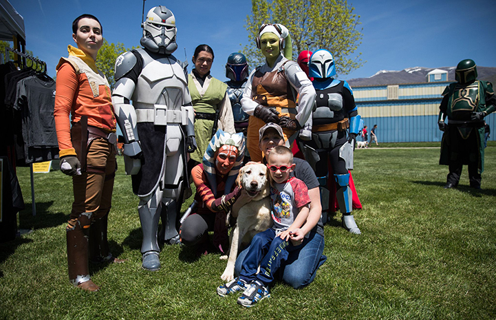 Family who adopted Keela the dog surrounded by many Star Wars characters at the May the 4th NKUT Super Adoption event
