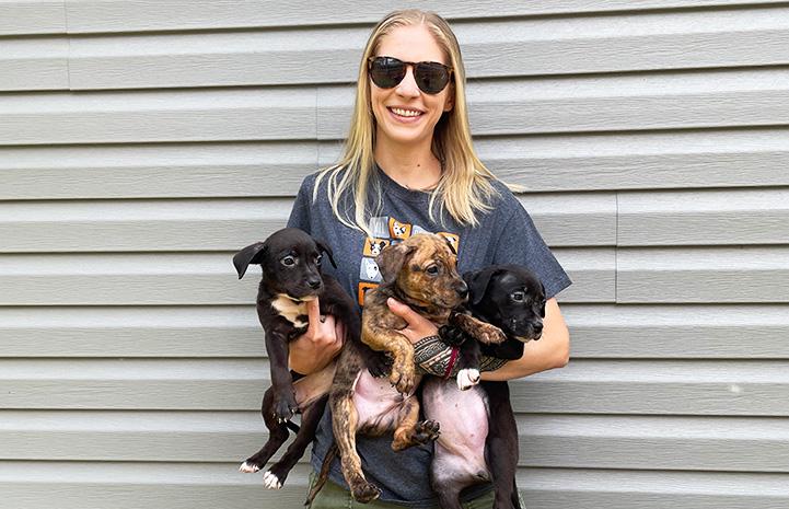 NWA volunteer Becca Beyer holding three puppies