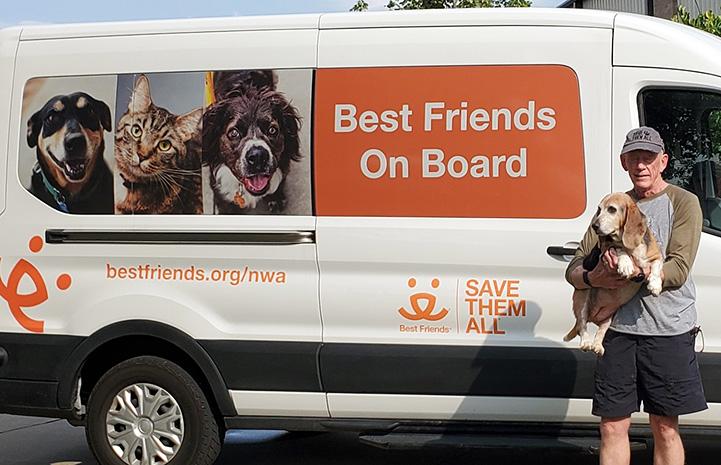 NWA volunteer Roy Horan holding a dog in front of a Best Friends transport van