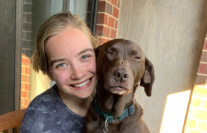 Carl the dog face-to-face next to the woman who adopted him