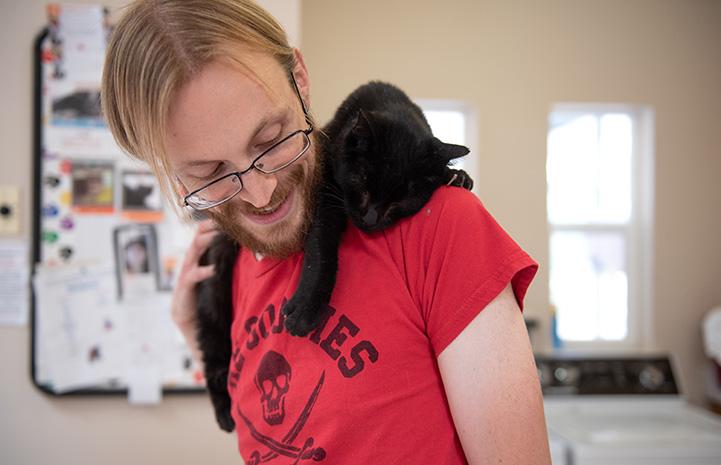 Black cat draped over the shoulder of male caregiver