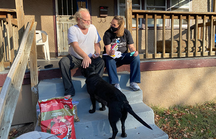 Kansas City Pet Project animal services team member on a porch giving a man some dog food while the man pets a black Lab