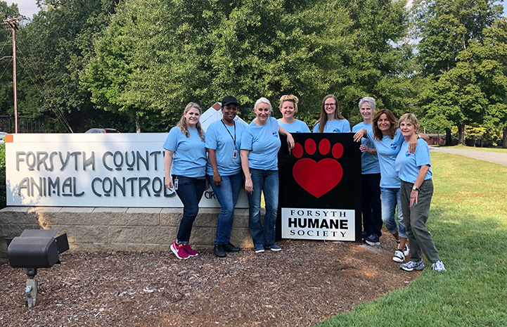 People standing in front of the Forsyth Humane Society sign