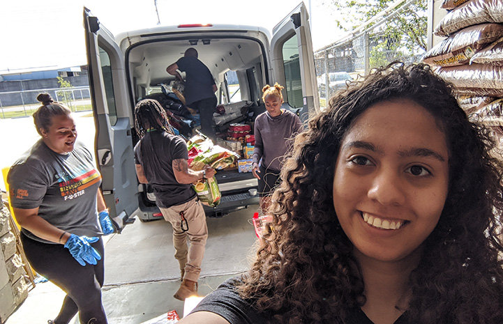 People loading a van with donated pet food to distribute