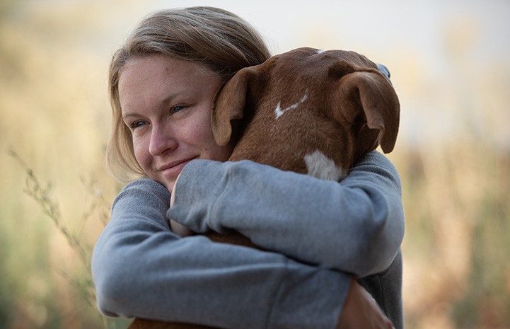 Woman hugging a brown dog