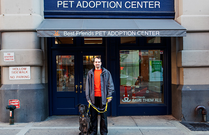 Volunteer Fabio Vitolla standing with a dog in front of the Best Friends Lifesaving Center in New York City