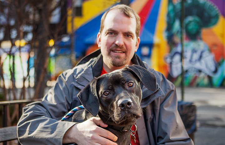 Volunteer Fabio Vitolla with his arm around a large black dog with a colorful background behind them