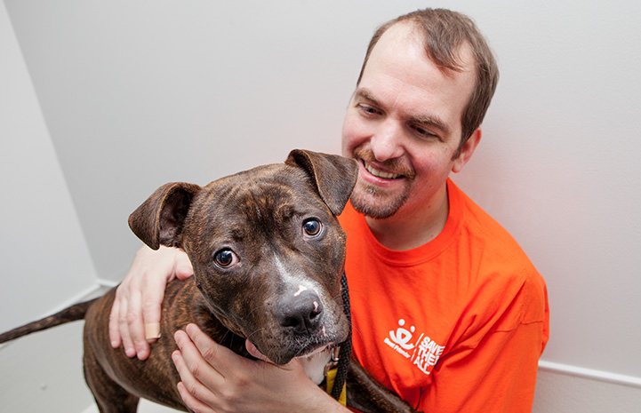 Volunteer Fabio Vitolla smiling and wearing an orange Best Friends T-shirt, sitting next to a large gray dog