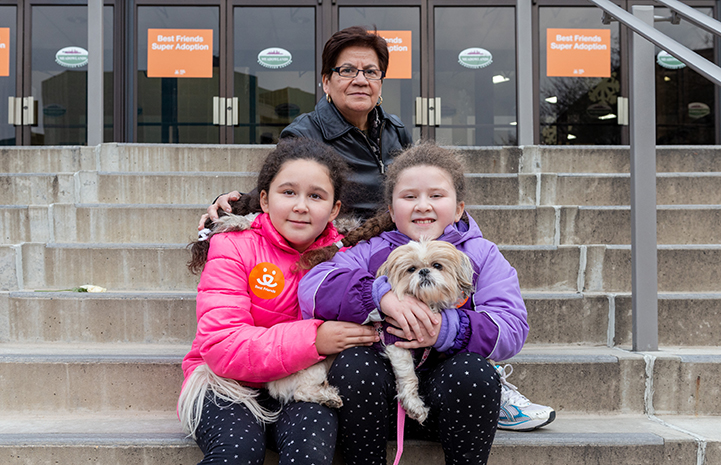Family holding a Maltese-type dog on some steps after adopting him from the New York Super Adoption