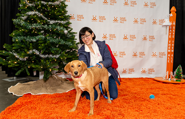 Woman and brown dog on an orange carpet in front of a Best Friends backdrop and Christmas tree