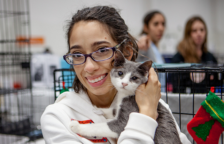 Smiling woman holding a gray and white cat