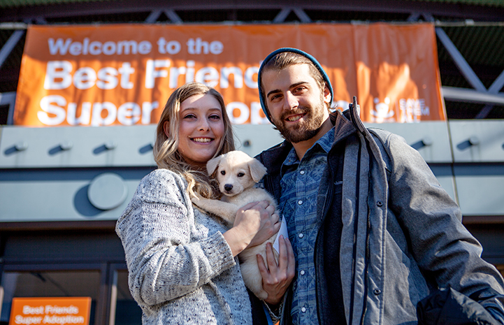 Couple holding a small blond puppy in front of a New York Super Adoption banner