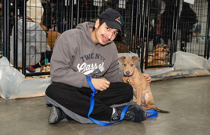 Man sitting on the ground next to a brown puppy during the New York Super Adoption