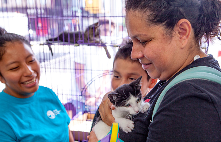 Smiling woman holding a black and white kitten while two people watch them at the New York cat adoption event