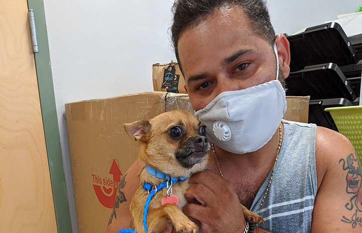 Masked man holding Chubbs the dog