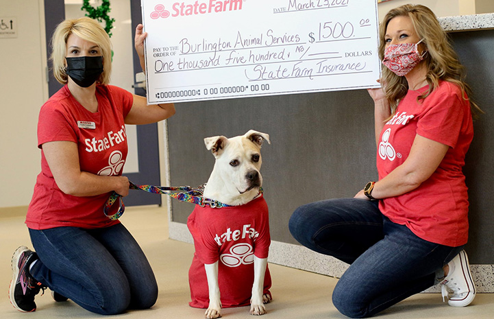 Jake from State Farm the dog with two people and an oversized check for $1,500 to the shelter from State Farm