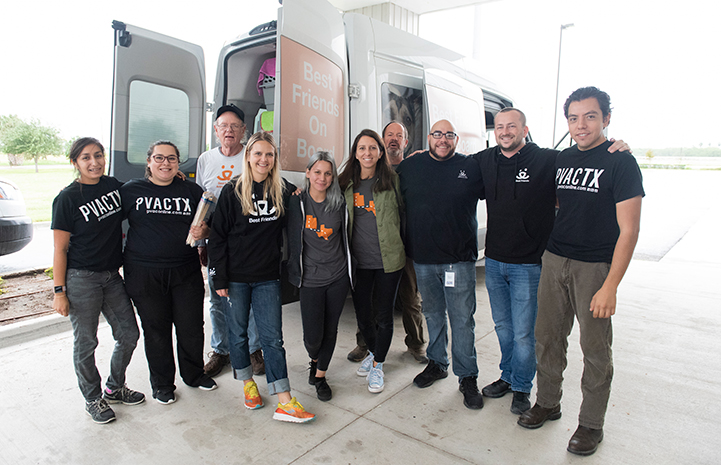 Group of people standing in front of a transport van