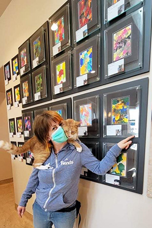Woman with a cat on her shoulders pointing at the wall of cat paintings