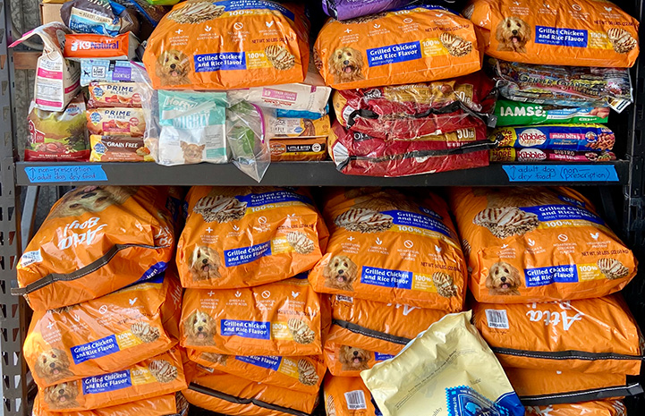 Multiple bags of dog food stacked on top of each other