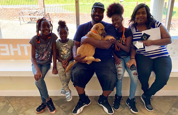 Smiling family of five adopting a puppy