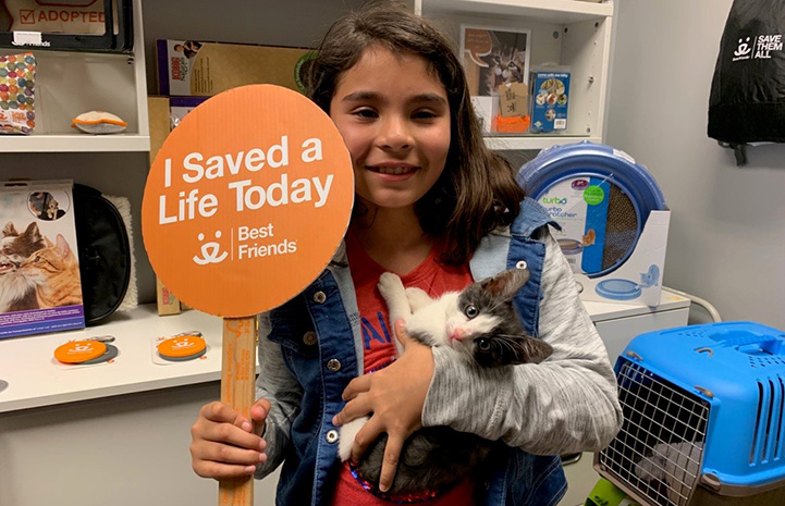 """Young girl with a kitten she adopted, holding a sign that says, """"I saved a life today"""""""