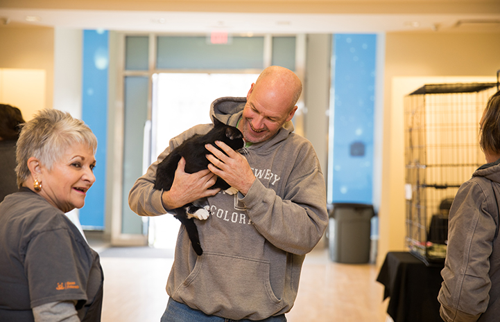 Man smiling and holding a black and white cat at the Save Them All Saturday in Salt Lake City