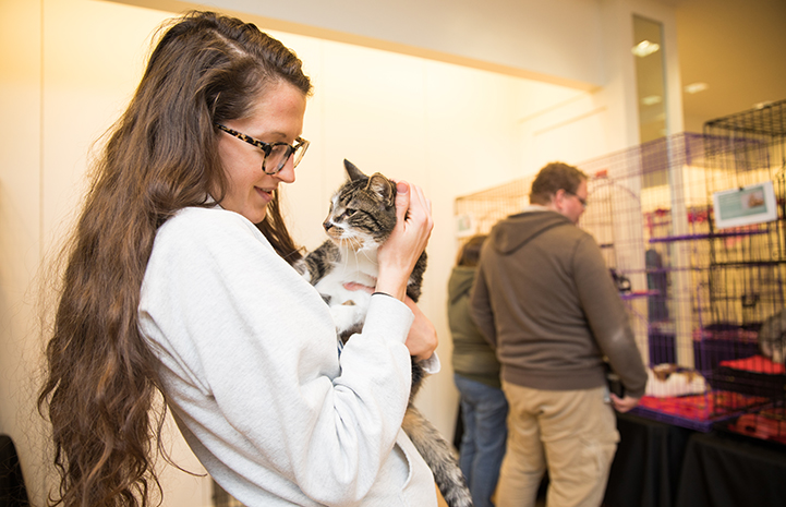 Sriracha, the brown tabby with white cat being held by a woman wearing glasses at the Save Them All Saturday in Salt Lake City