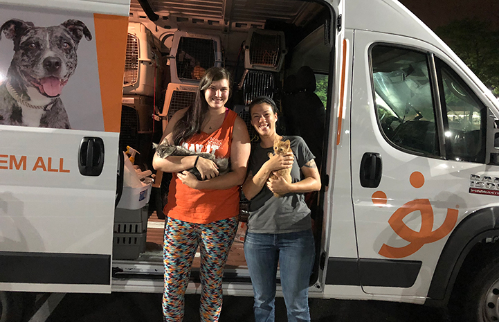 Two woman holding cats in front of the Best Friends transport van
